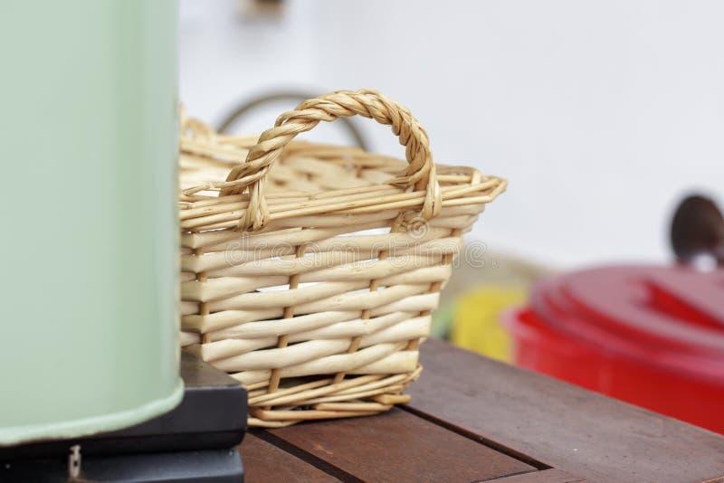 在一个绿色金属箱子后的小柳条筐陶器的 库存照片
