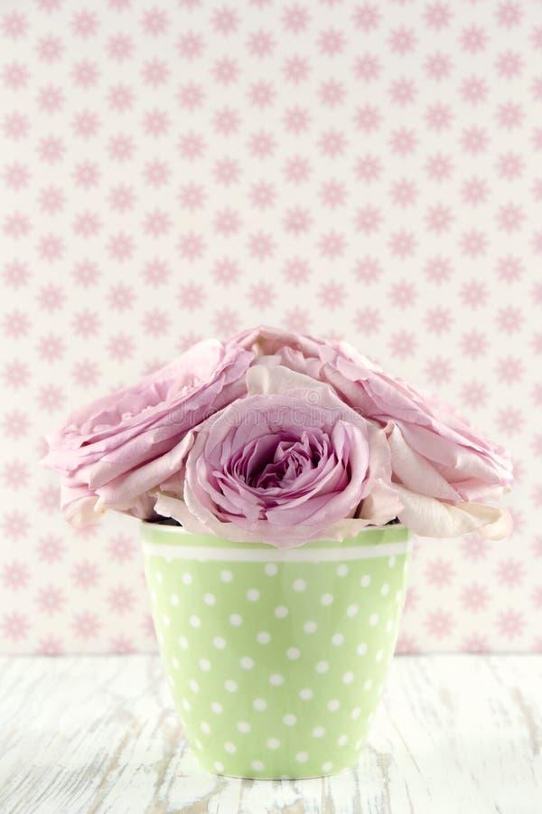 在一个绿色polkadot花瓶的花在葡萄酒木背景 免版税图库摄影