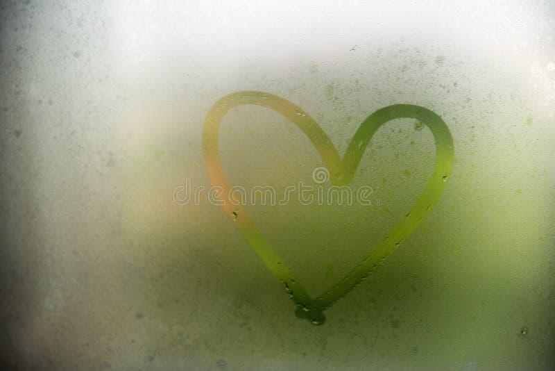 在一个misted窗口绘的心脏 在misted玻璃的心脏 在窗口背景的心脏 免版税库存图片