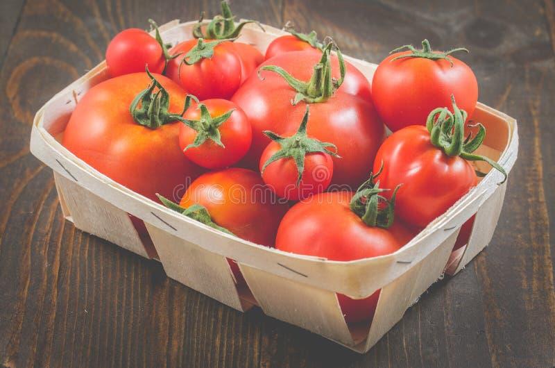 在一个wattled篮子的蕃茄在木背景/蕃茄在一个wattled容器在黑暗的木背景,选择聚焦 库存照片