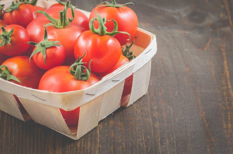 在一个wattled篮子/蕃茄的蕃茄在一黑暗的木背景、选择聚焦和copyspace的一个wattled容器 免版税库存照片