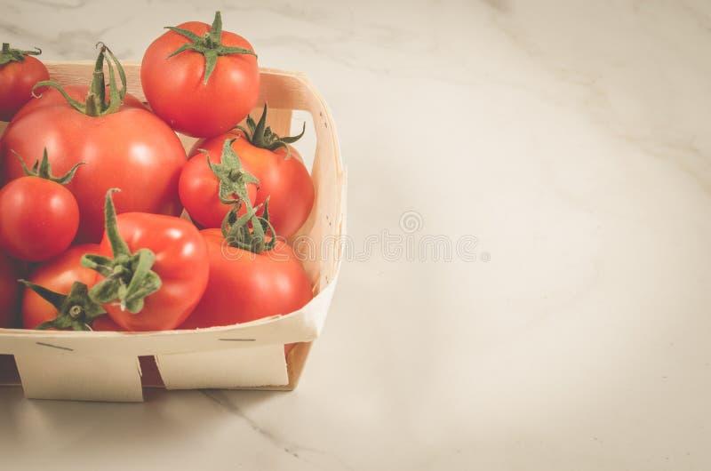 在一个wattled篮子/蕃茄的蕃茄在白色大理石背景的一个wattled篮子 顶视图和Copyspace 免版税库存照片