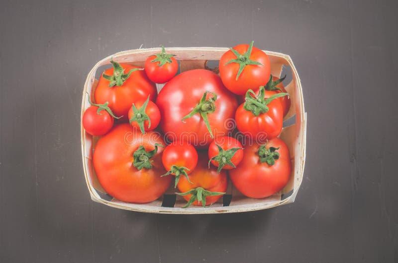 在一个wattled篮子/蕃茄的蕃茄在黑暗的背景,顶视图的一个wattled容器 免版税库存图片