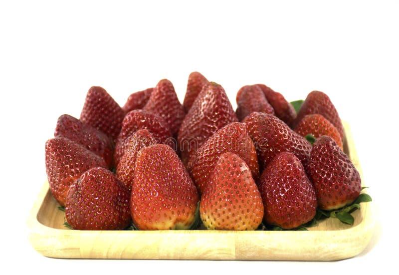 在一个wodden盘子的新鲜的草莓在被隔绝的背景中 免版税库存图片
