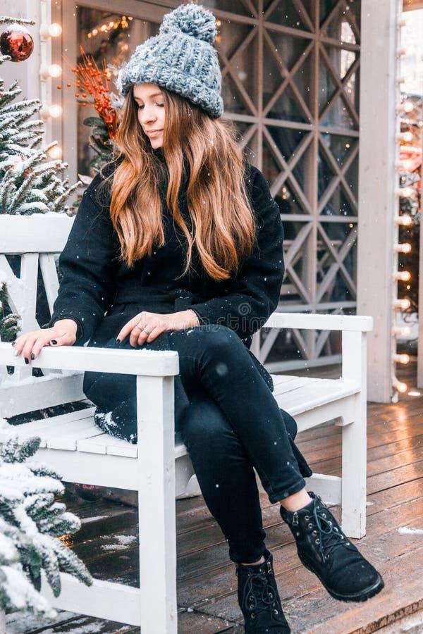 在一云彩天在冬天走在Tverskaya广场的美丽的俄国女孩及时圣诞节打过工 库存照片