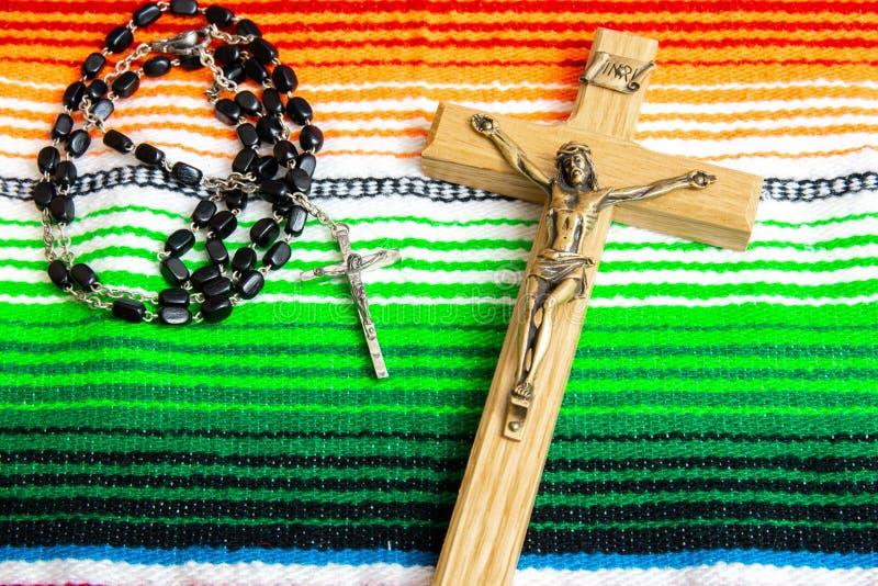 在一五颜六色的墨西哥sarape的耶稣受难象和念珠小珠 免版税库存图片