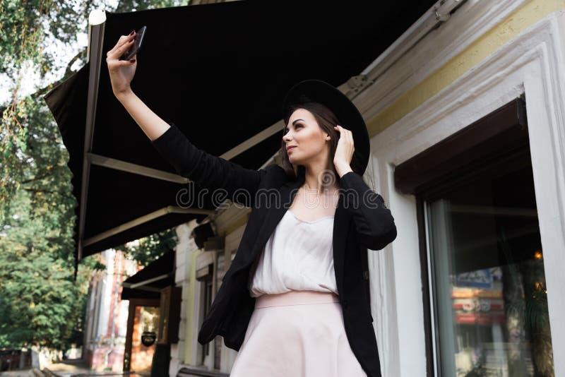在一件时髦的白色礼服、一件黑夹克和黑帽会议打扮的一个美丽的女孩在大理石咖啡桌和w附近站立 免版税库存照片
