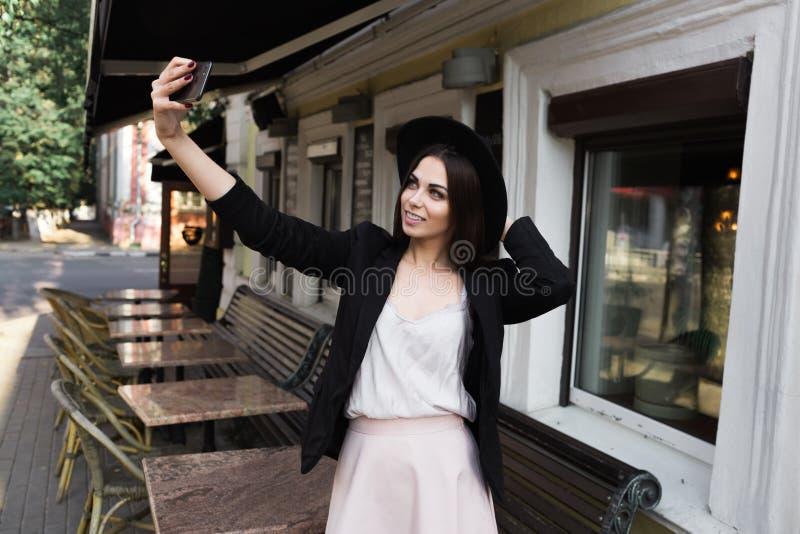 在一件时髦的白色礼服、一件黑夹克和黑帽会议打扮的一个美丽的女孩在大理石咖啡桌和w附近站立 库存图片