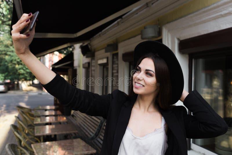 在一件时髦的白色礼服、一件黑夹克和黑帽会议打扮的一个美丽的女孩在大理石咖啡桌和w附近站立 库存照片