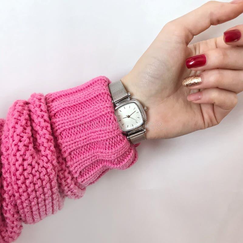 在一件桃红色毛线衣的女性手有时钟和美好的manicur的 库存图片