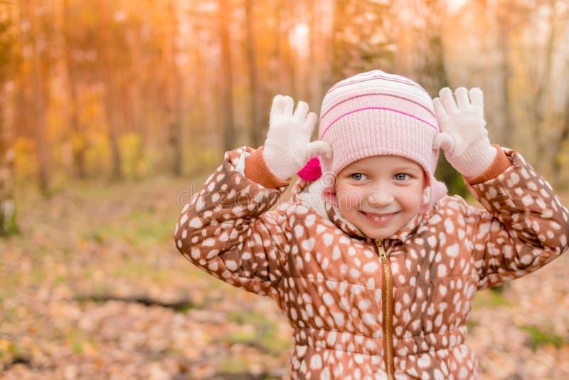 在一件温暖的外套打扮的一个滑稽的女孩站立与一张邪恶的面孔,婴孩显示老虎或鹿 滑稽逗人喜爱 免版税库存图片