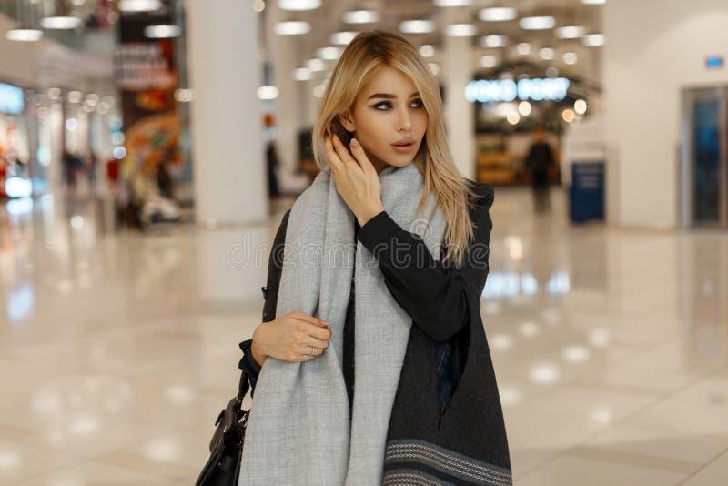 在一件灰色秋天时髦的外套的迷人的年轻女人模型有有一个皮革黑提包的葡萄酒温暖的围巾的 库存照片