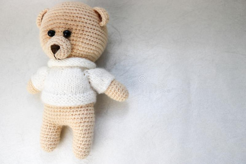 在一件白色毛线衣有黑眼睛的,一个软的玩具的一头被编织的自创美丽的逗人喜爱的小的熊栓与在锂的米黄大螺纹 图库摄影