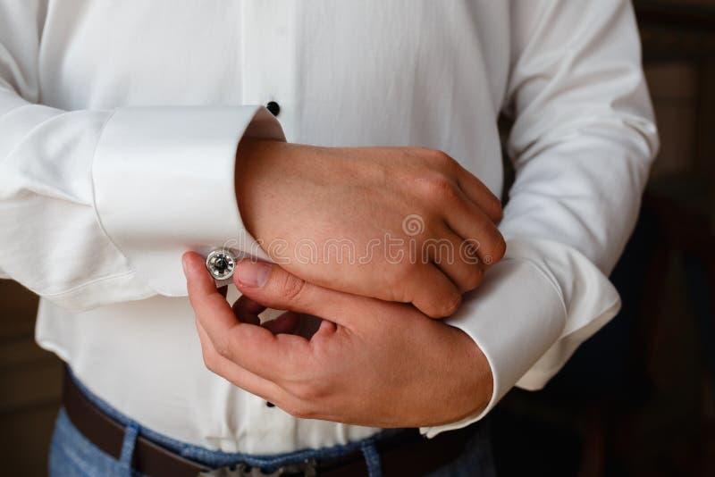 在一件白色衬衣的商人调直袖口,站立在自然光的窗口 人按在法国人袖口sle的链扣 免版税库存照片