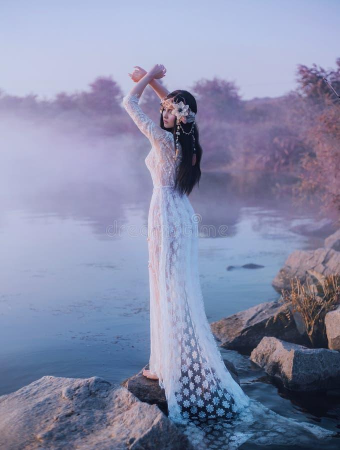 在一件白色鞋带礼服的一个河若虫在岩石站立在湖旁边 公主有与贝壳的一个美丽的花圈 库存照片
