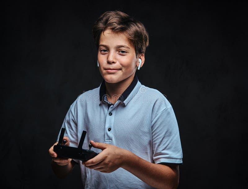 在一件白色T恤杉打扮的一个年轻男孩的画象佩带一个无线耳机举行控制遥控 在黑暗 图库摄影