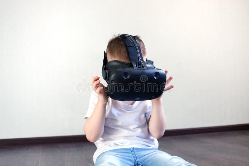 在一件白色T恤杉的男孩白肤金发的4岁有虚拟现实,现代技术,靛蓝孩子盔甲的  免版税库存照片