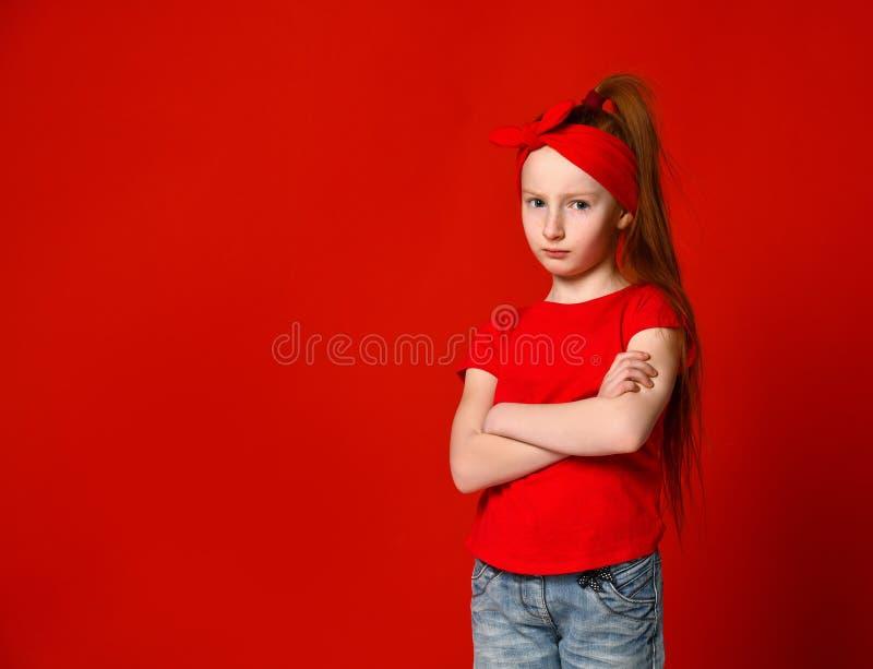 在一件红色背心让烦恼的一个逗人喜爱的女孩的画象,站立用被折叠的手和看照相机 免版税图库摄影