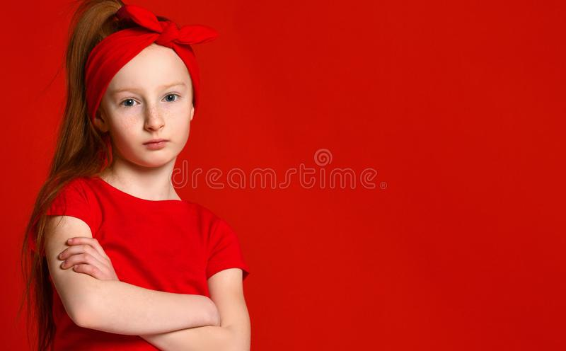 在一件红色背心让烦恼的一个逗人喜爱的女孩的画象,站立用被折叠的手和看照相机 免版税库存图片