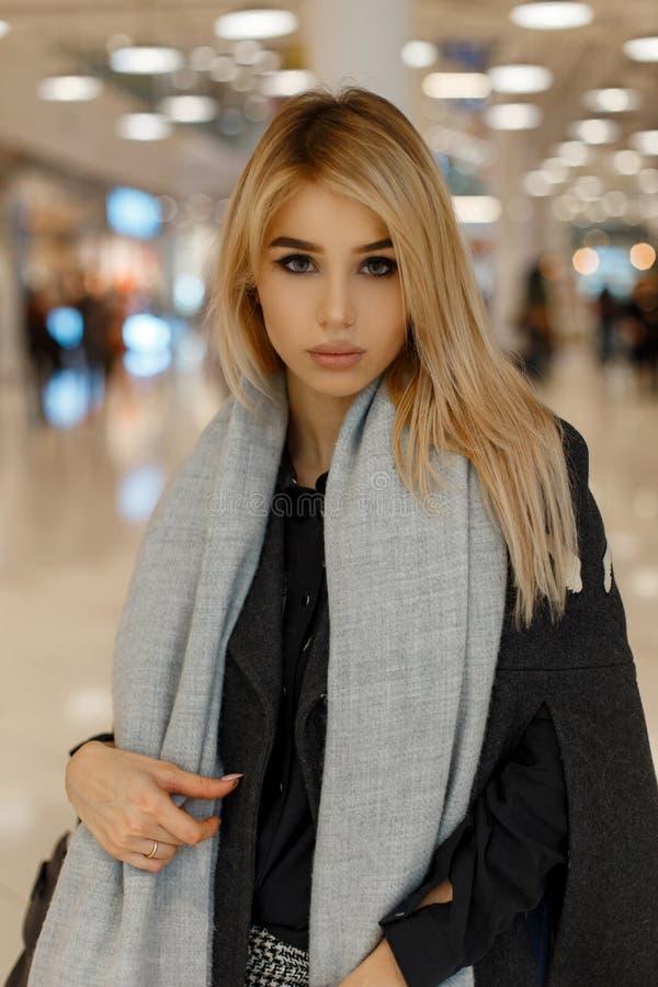 在一件豪华时髦葡萄酒葡萄酒外套的年轻有吸引力的妇女模型有一条时兴的温暖的围巾的去购物 免版税库存图片