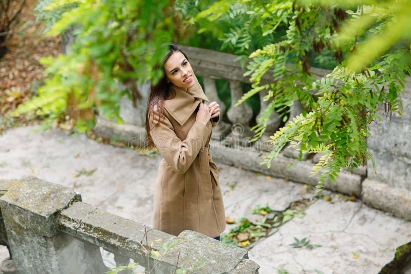 在一件轻的外套打扮的一个女孩沿外部走 免版税库存照片