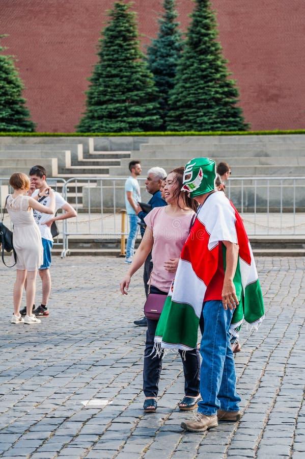在一件雨披的墨西哥爱好者在旗子的颜色和在面具在红场被拍摄 库存图片