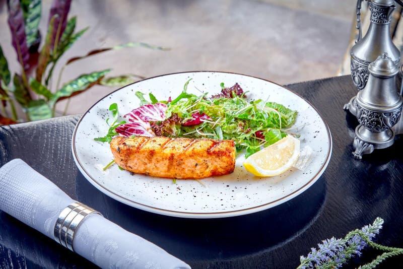 在一件鲑鱼排的接近的看法用蔬菜沙拉和柠檬在白色板材 餐馆食物背景 r ?? 免版税库存图片