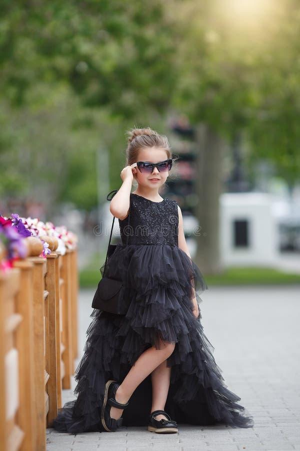 在一件黑晚礼服打扮的逗人喜爱的深色的女孩,走户外 免版税库存照片
