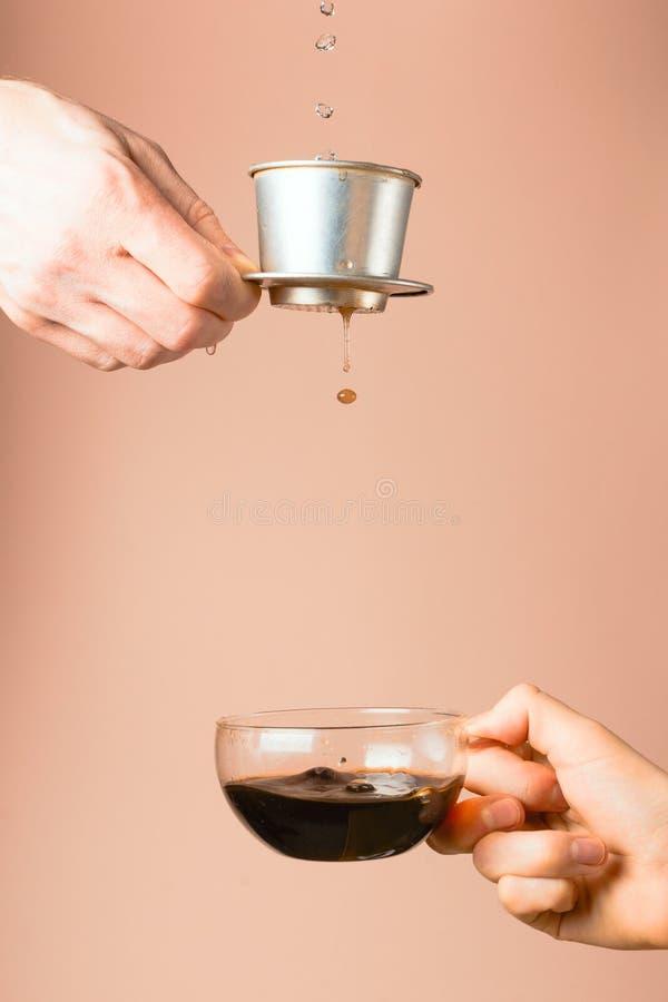 在一份人` s手倾吐的咖啡的越南咖啡过滤器到一个杯子里在妇女` s手上 免版税库存照片
