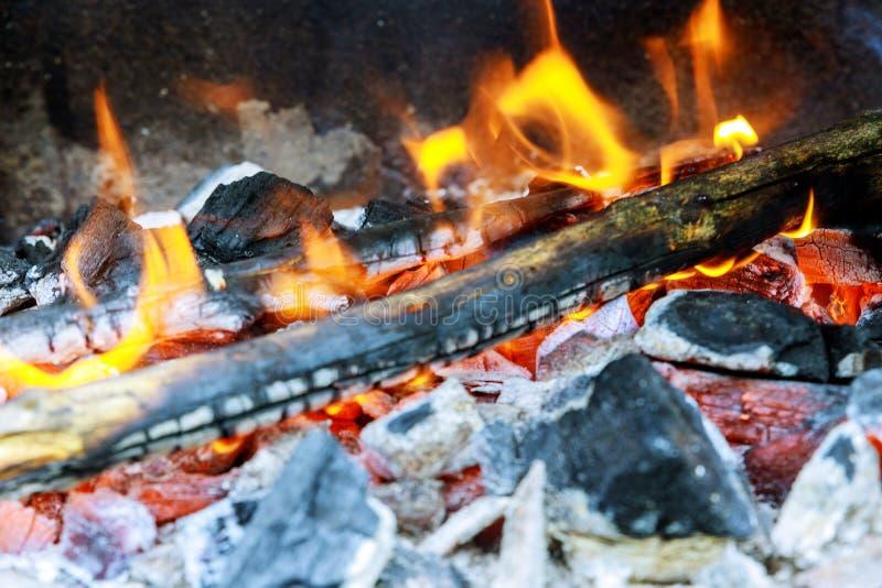 在一位火盆的木柴燃烧在明亮的黄色火焰树,在金属火盆里面的深灰煤炭 库存照片