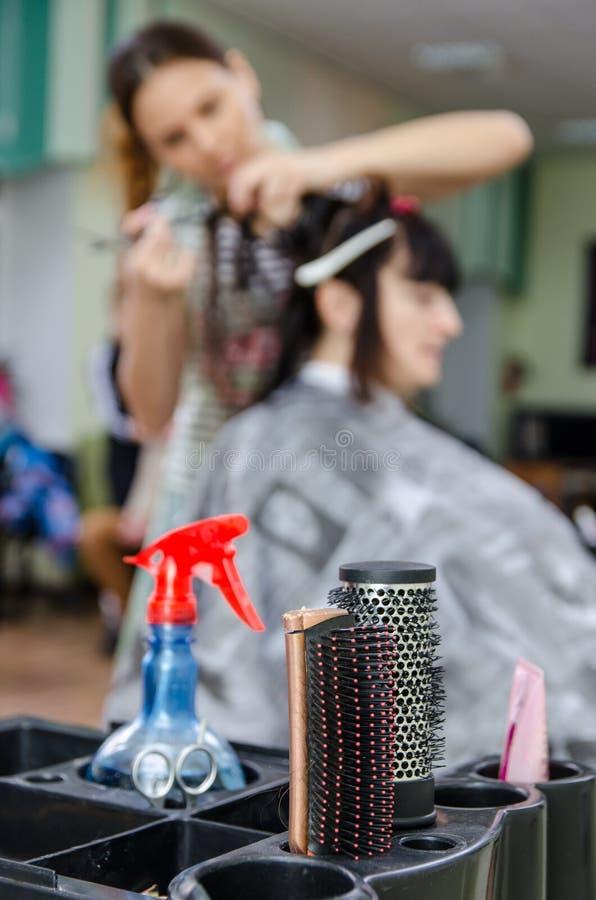 在一位职业妇女美发师的背景的美发师工具 图库摄影