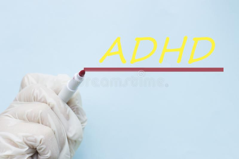 在一副手套的医生的手与一支毡尖的笔,ADHD注意力不集中活动过度混乱 免版税库存图片