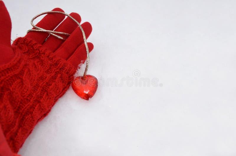 在一副红色手套的女性手说谎在雪和在红心附近 图象 免版税库存图片