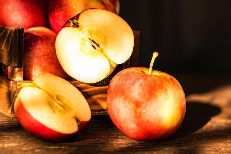 关闭整个成熟红色苹果并且切开在木箱的一半木表面上有黑背景 选择图片