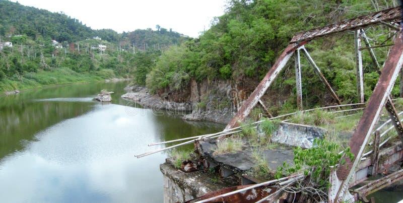 在一半部分地打破的一座老生锈的桥梁在hurricaine以后 免版税图库摄影