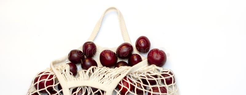 在一只生态棉花可再用的网兜,一个选择的李子到塑料袋,在白色背景 r 免版税库存照片