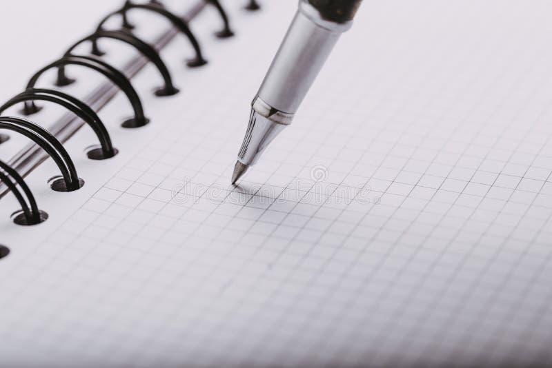 在一只笼子的被打开的笔记薄与一个自动塑料圆珠笔特写镜头 o 库存例证