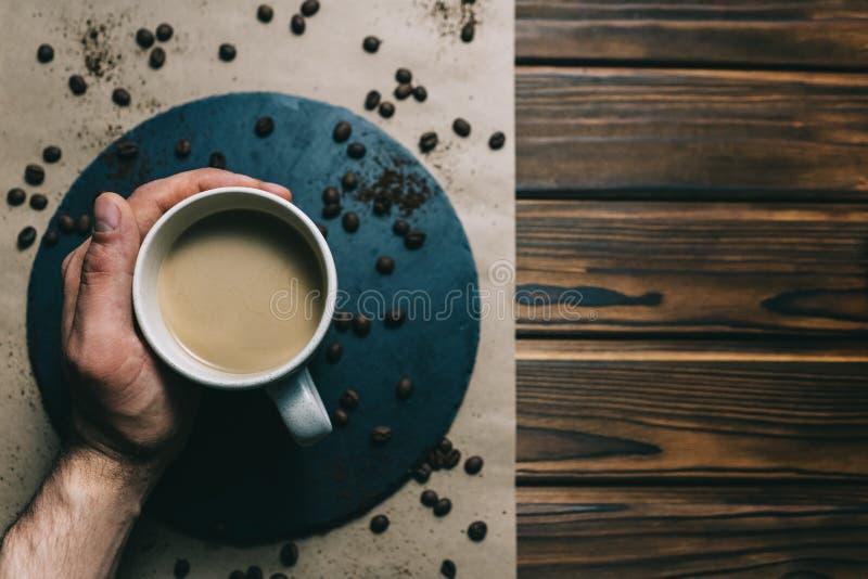 在一台磨丝器的咖啡有在手中一个杯子的在与奶油的黑暗的背景 免版税图库摄影