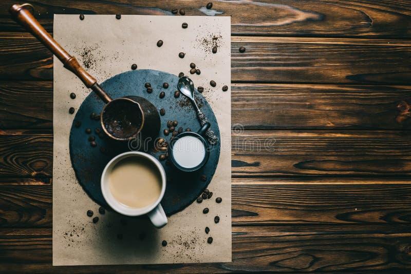 在一台磨丝器的咖啡有在黑暗的背景的一个杯子的与奶油 免版税库存照片