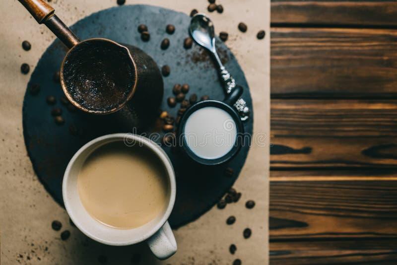 在一台磨丝器的咖啡有在黑暗的背景的一个杯子的与奶油 图库摄影