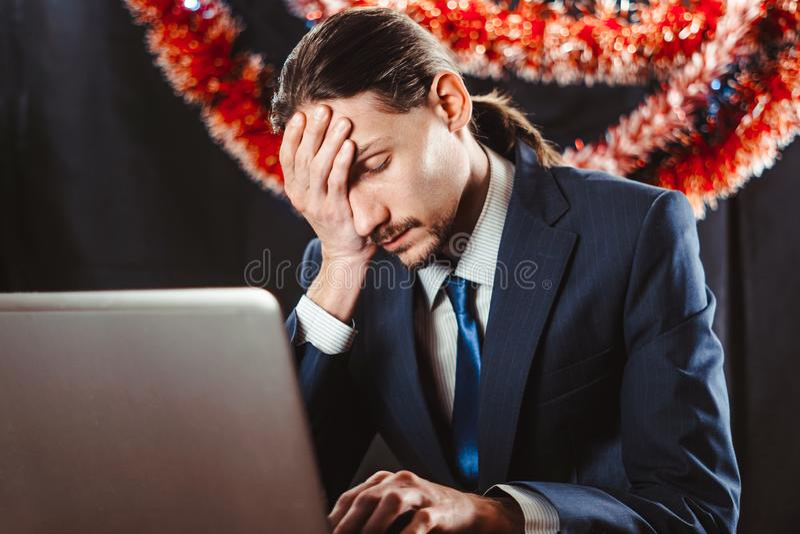 在一台膝上型计算机后的商人在新年 库存图片