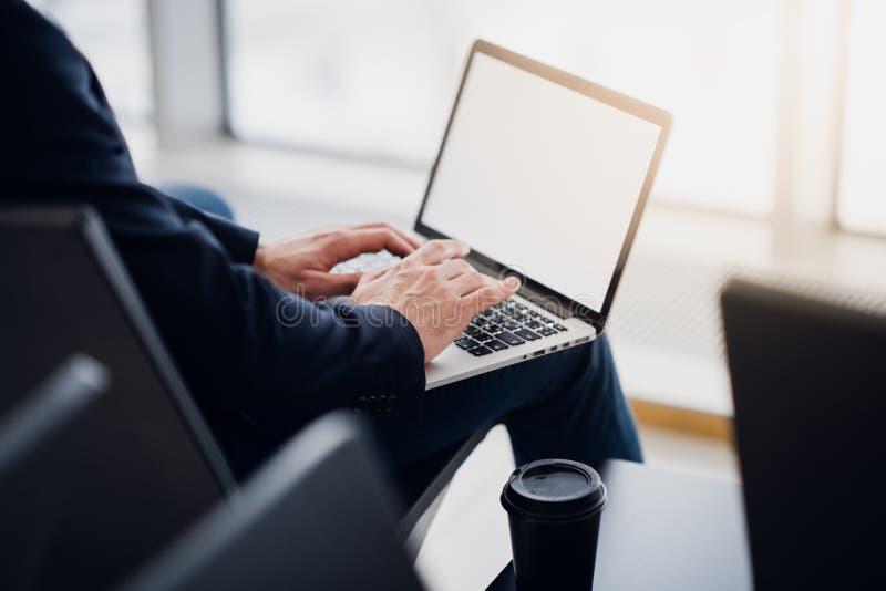 在一台膝上型计算机的商人手使用Wi-Fi互联网在机场 一个人的手的特写镜头键入在键盘的消息 免版税库存图片