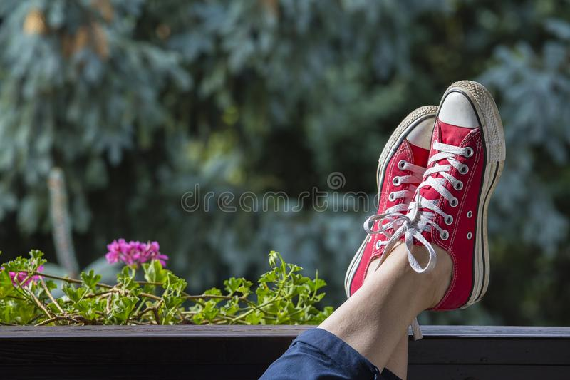 在一名妇女的腿的红色运动鞋以自然为背景的 库存照片