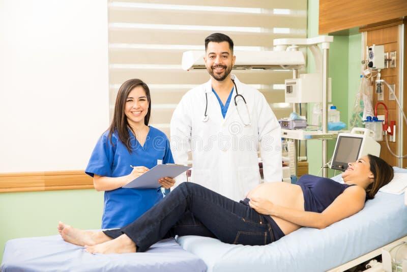 在一名孕妇旁边的西班牙医生 库存照片