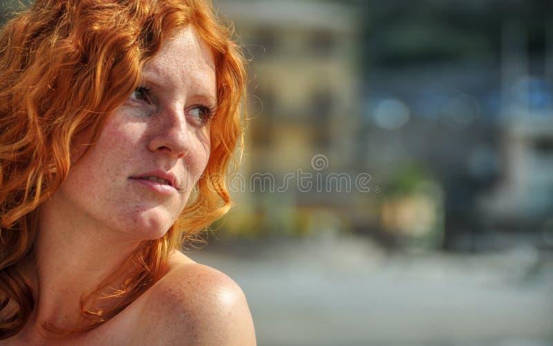 在一名年轻典雅的红发卷曲妇女的特写镜头的美丽的画象由海的渔村的在有拷贝空间的意大利 免版税库存照片