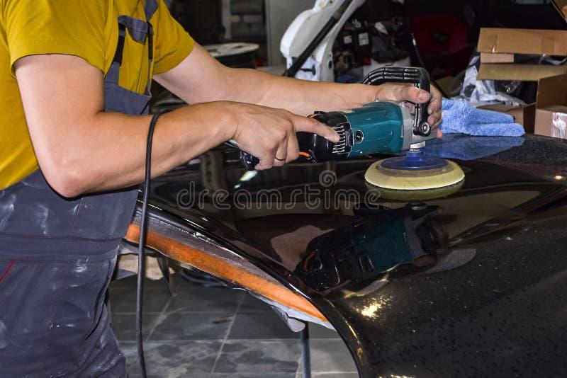 在一名男性工作者的手上的特写镜头视图拿着为擦亮汽车敞篷的一个工具,当工作在a时的黄色衬衣的 免版税库存图片