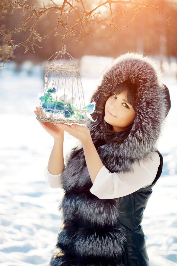 在一名笼子冬天妇女的少妇和冬天鸟backgroun的 图库摄影