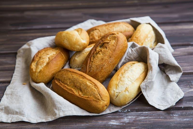 在一块亚麻制毛巾的新近地被烘烤的面包小圆面包, Wonder面包小圆面包堆积 库存照片