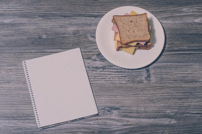在一块圆的白色板材的鲜美三明治有在灰色木背景的笔记本的 顶视图 葡萄酒作用 库存照片