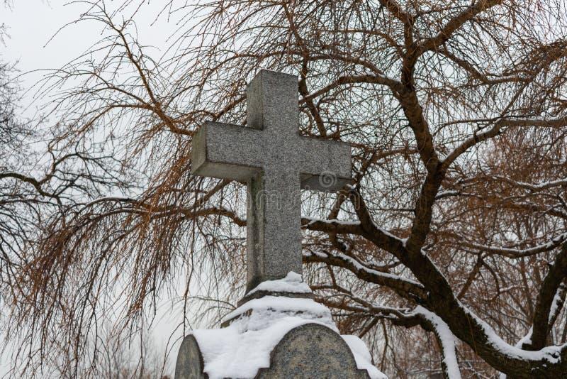 在一块墓碑顶部的十字架在一座公墓在与雪的冬天 免版税库存照片